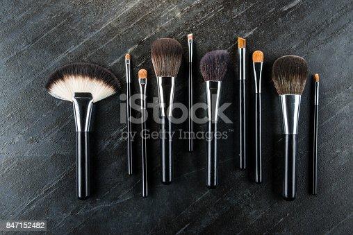 847152928 istock photo fashion cosmetic brush set arrange on stone floor 847152482