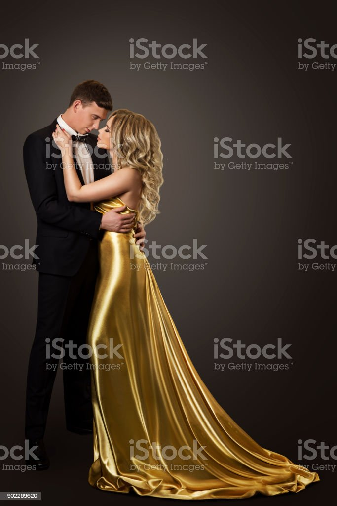 Fashion Couple Beauty Portrait, Kissing Man and Woman, Well Dressed in Golden Dress and Black Suit stock photo