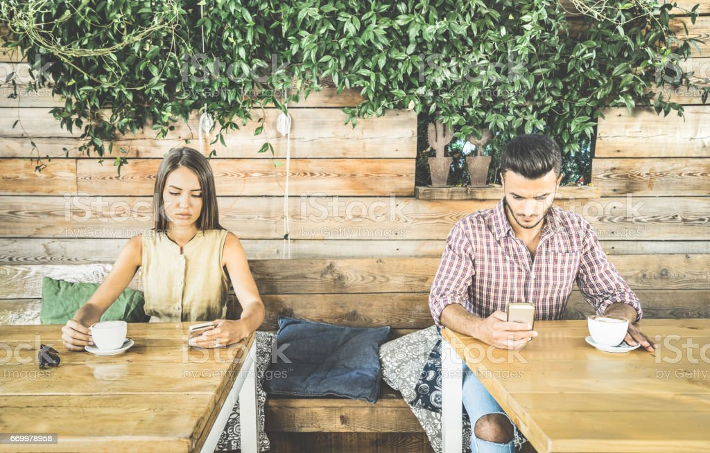Fashion couple in disinterest moment ignoring each other using mobile cell phone - Concept of apathy sadness addicted to new technologies - Boyfriend and girlfriend break up with smartphones addiction stock photo