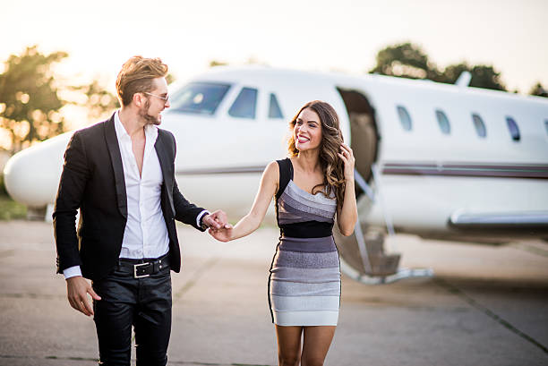 Fashion couple leaving the private jet airplane stock photo