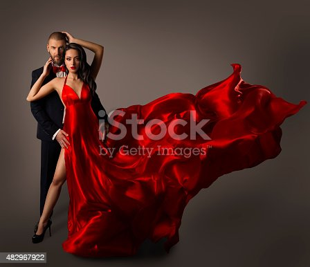 istock Fashion Couple Portrait, Woman Red Dress, Man Suit, Flying Cloth 482967922