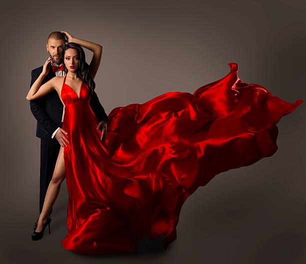 mode paar porträt, frau roten kleid mit fliegenden stoff mann anzug, - lange abendkleider stock-fotos und bilder