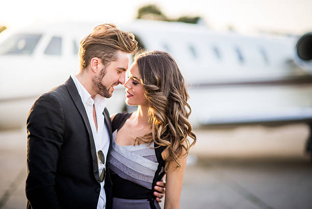 fashion couple sharing a hug at the airport track - love at first sight stock photos and pictures