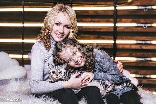 istock Fashion cute little girl and beautiful woman with a British kitten in the arms of very happy 1080927020