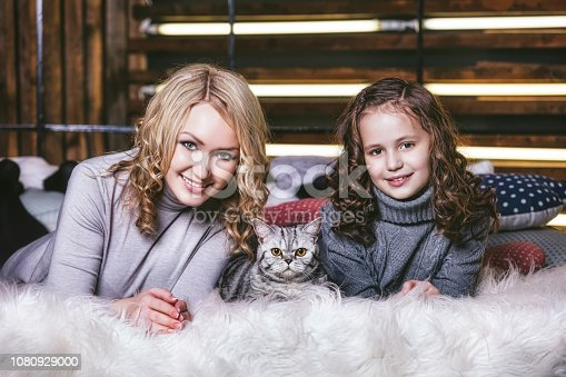 istock Fashion cute little girl and beautiful woman with a British kitten in the arms of very happy 1080929000
