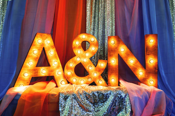 Fashion design element for wedding ceremonies, banquets, parties decoration - wooden letters (first letters in names of bride and groom) with light bulbs and sparkling fabric. stock photo