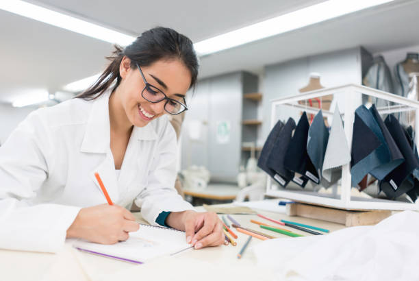 Fashion design student at the atelier drawing sketches Portrait of a Latin American fashion design student at the atelier drawing sketches and smiling designer baby stock pictures, royalty-free photos & images