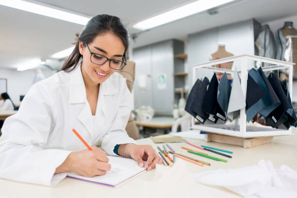 Fashion design student taking notes at the university Portrait of a female fashion design student taking notes at the university - education concepts designer baby stock pictures, royalty-free photos & images