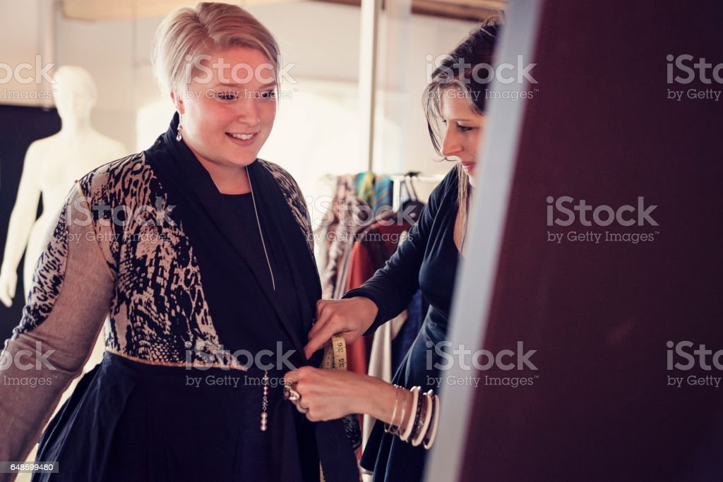 Fashion designer adjusting clothing on plus size woman. stock photo