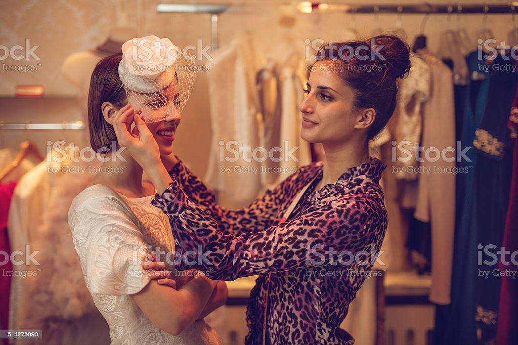 Fashion designer adjusting lace on bride's hat in design studio. stock photo