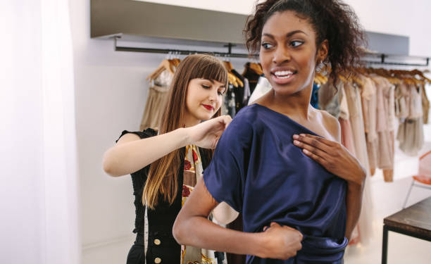 Fashion designer designing clothes in her fashion design studio along with a model Fashion designer trying new designer clothes on a model. Woman entrepreneur in her cloth shop designing new clothes. fashion designer stock pictures, royalty-free photos & images