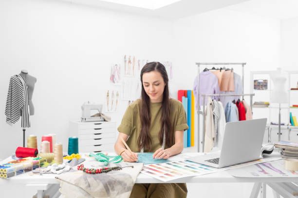 fashion designer drawing a concept a young fashion designer drawing at the desk in her showroom fashion designer stock pictures, royalty-free photos & images