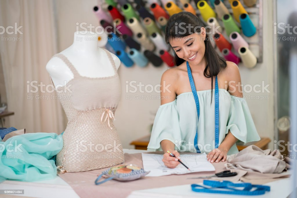 Fashion designer drawing a dress pattern at an atelier stock photo