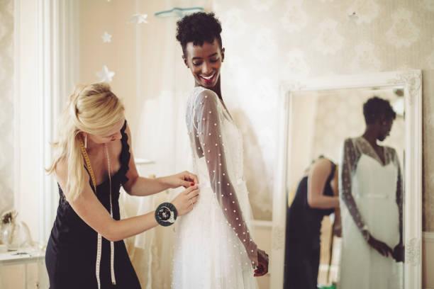 Fashion designer is adjusting the wedding dress stock photo