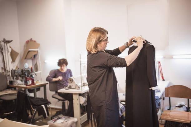 mode-designer, reife modische dame arbeiten im atelier - barbiekleidung stock-fotos und bilder