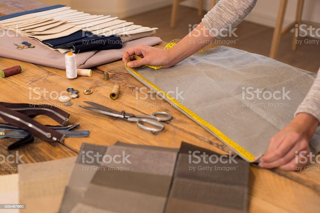 Fashion designer measuring cloth stock photo