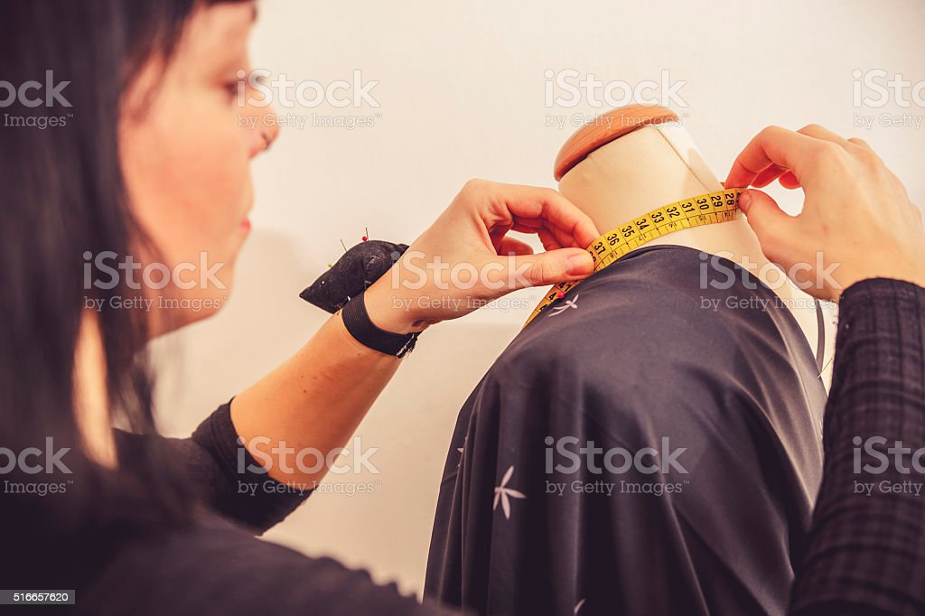 Fashion Designer Measuring Dress Form on Tailor's Dummy, Close-up stock photo