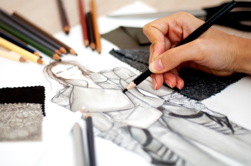 Fashion designer is drawing an artistic fashion sketch ,close-up photo