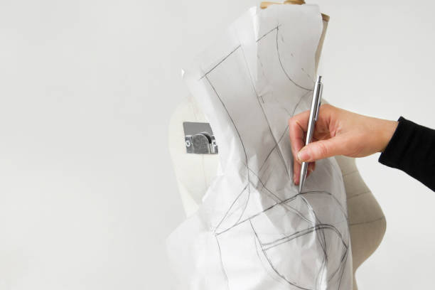 Fashion Designer Putting Dress Templates on Mannequin Female fashion designer or student is working on her new dress for homework. fashion designer stock pictures, royalty-free photos & images
