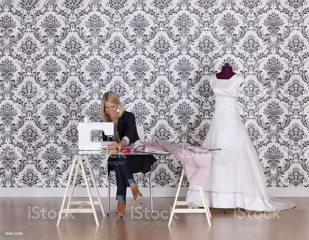 Fashion designer sewing a dress in her workshop royalty-free stock photo