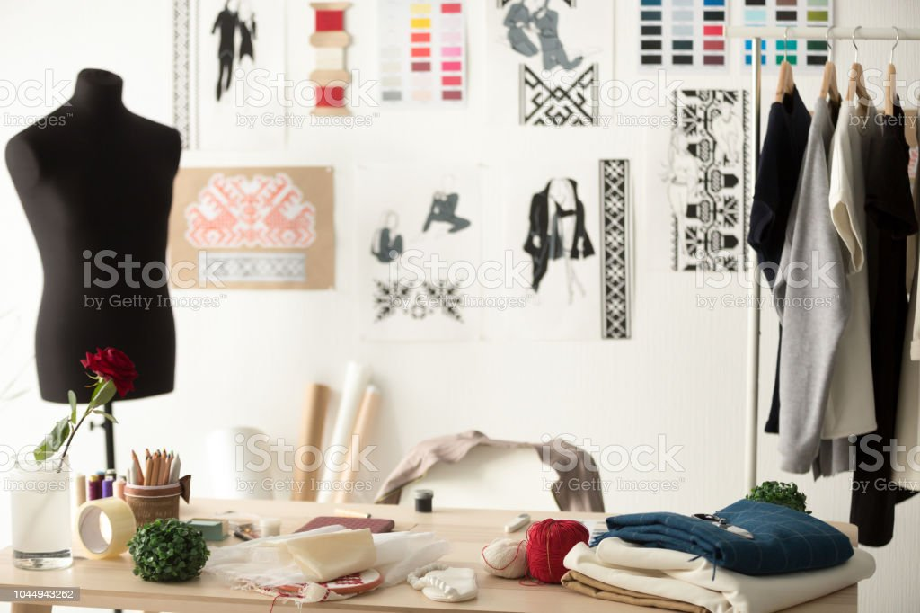Fashion designer showroom with mannequin, work desk and clothes stock photo