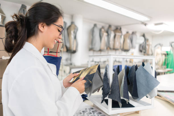 Fashion designer student looking at fabrics Portrait of a happy female fashion designer student looking at fabrics in class - education concepts designer baby stock pictures, royalty-free photos & images
