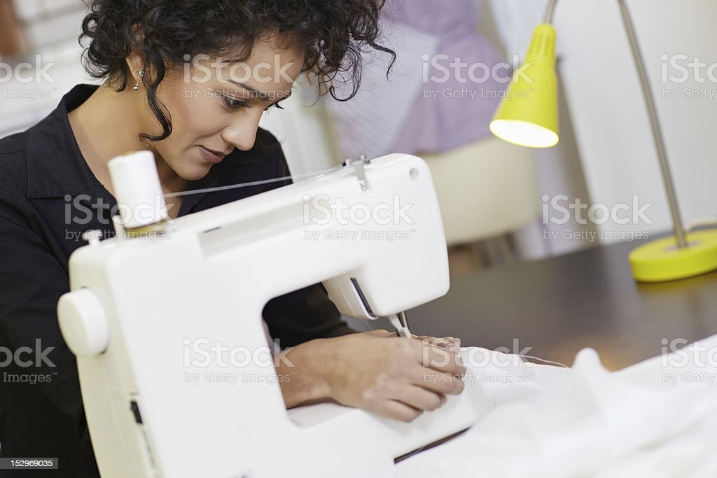 A fashion designer using a sewing machine royalty-free stock photo