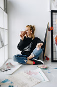 young female fashion designer drinking coffee and eating macaroons in office