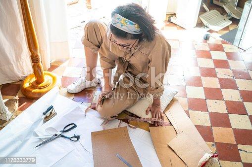 Fashion designer woking in sewing patterns sitting on the floor at vintage studio