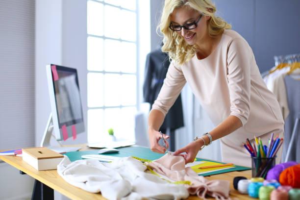 Mode-Designerin Frau an ihre Entwürfe im Studio arbeiten. – Foto