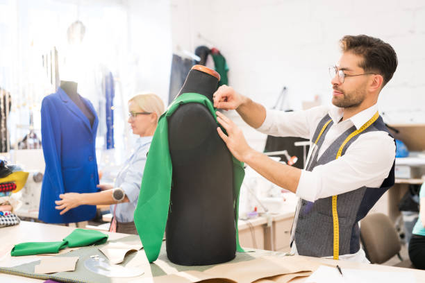 Fashion Designer Working in Atelier Side view portrait of mature tailor working with mannequin in atelier workshop, copy space fashion designer stock pictures, royalty-free photos & images