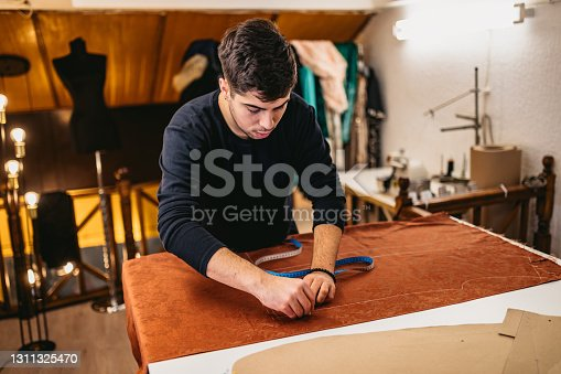 Young fashion designer working in atelier with sewing pattern.