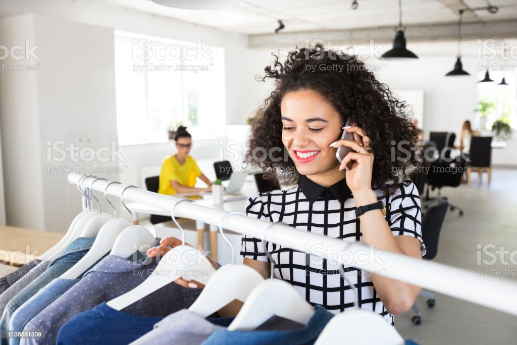 Fashion designer working in modern workplace Smiling young woman looking at the clothes on the rack and talking on mobile phone in office 20-24 Years Stock Photo