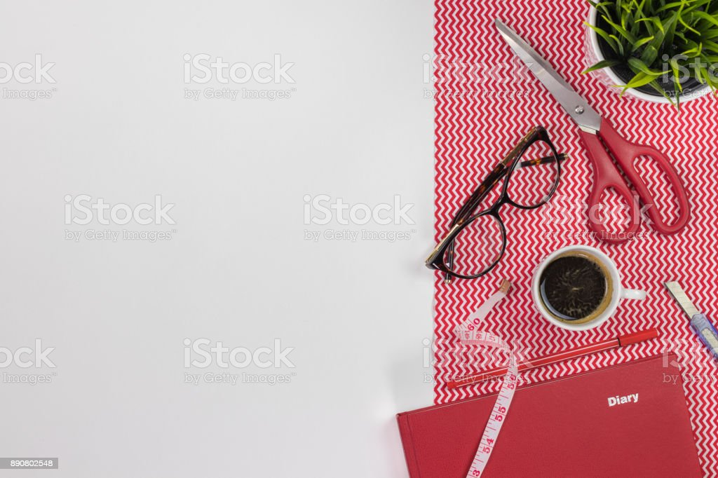 Fashion designer workplace. Modern white office desk table with a notebook diary, pen, eyeglasses and cup of coffee. stock photo