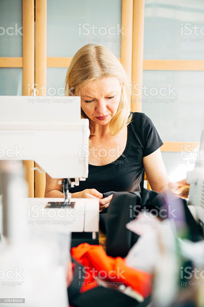 Fashion designer works at Sewing Machine royalty-free stock photo