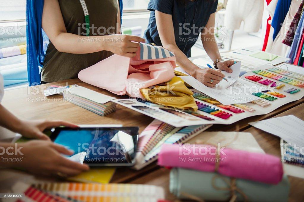 Three female workers meeting in Fashion design studio.