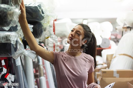 1083251186istockphoto Fashion disagner choosing a fabric in a store 1090610030