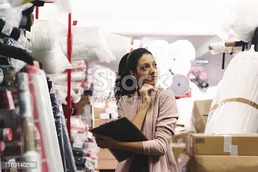 1083251186istockphoto Fashion disagner choosing a fabric in a store 1169140295