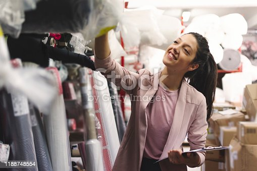 1083251186istockphoto Fashion disagner choosing a fabric in a store 1188748554