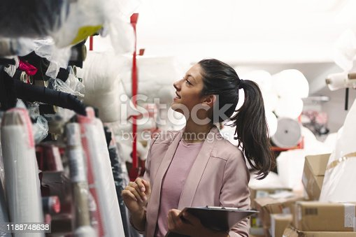 1083251186istockphoto Fashion disagner choosing a fabric in a store 1188748638