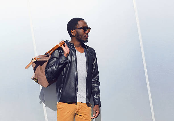 fashion elegant african man with bag in city - mode urbaine photos et images de collection