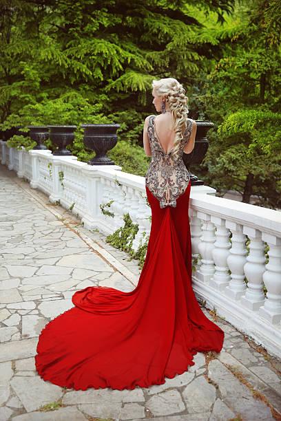 fashion elegant blond woman model in red gown with train - lange abendkleider stock-fotos und bilder