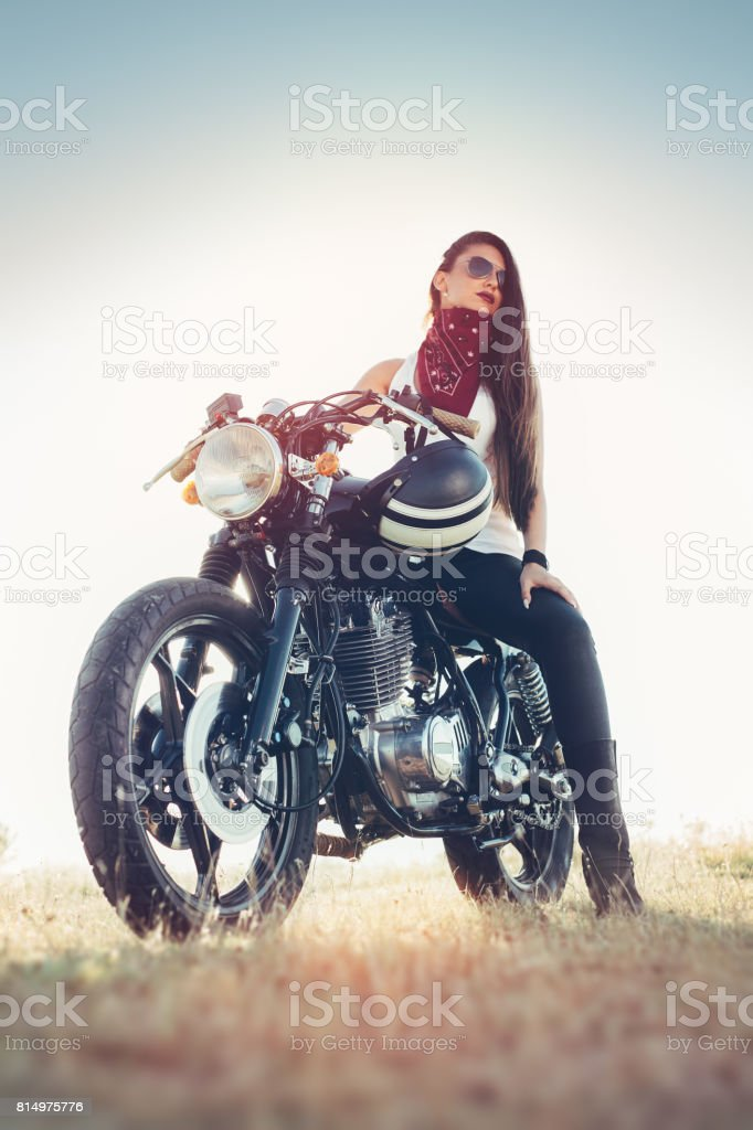 Fashion female biker girl. Young Woman sitting on vintage custom motorbike. stock photo