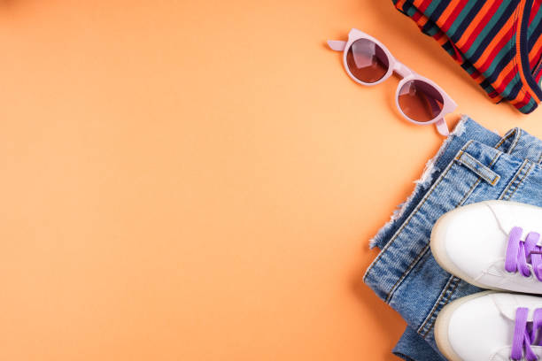 Fashion flat lay with jeans and glasses on orange stock photo