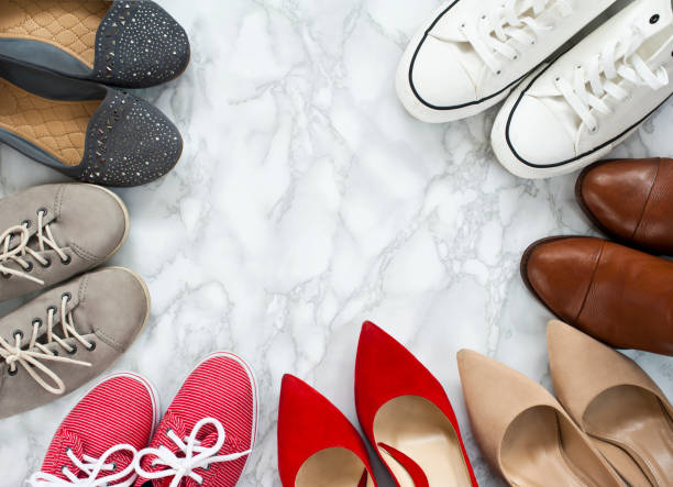 Fashion flatlay - variety of the colorful woman shoes on white, marble, elegant background. stock photo