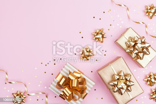 istock Fashion gifts or presents boxes with golden bows and star confetti on pink top view. Flat lay composition for birthday, christmas or wedding. 1065832542