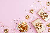 Fashion gifts or presents boxes with golden bows and star confetti on pink top view. Flat lay composition for birthday, christmas or wedding.