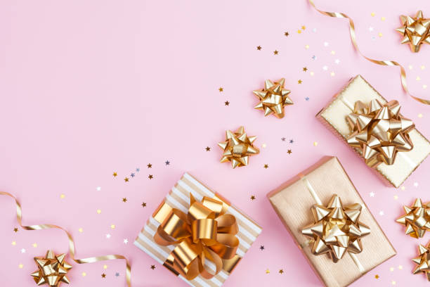 fashion gifts or presents boxes with golden bows and star confetti on pink top view. flat lay composition for birthday, christmas or wedding. - regalo natale foto e immagini stock