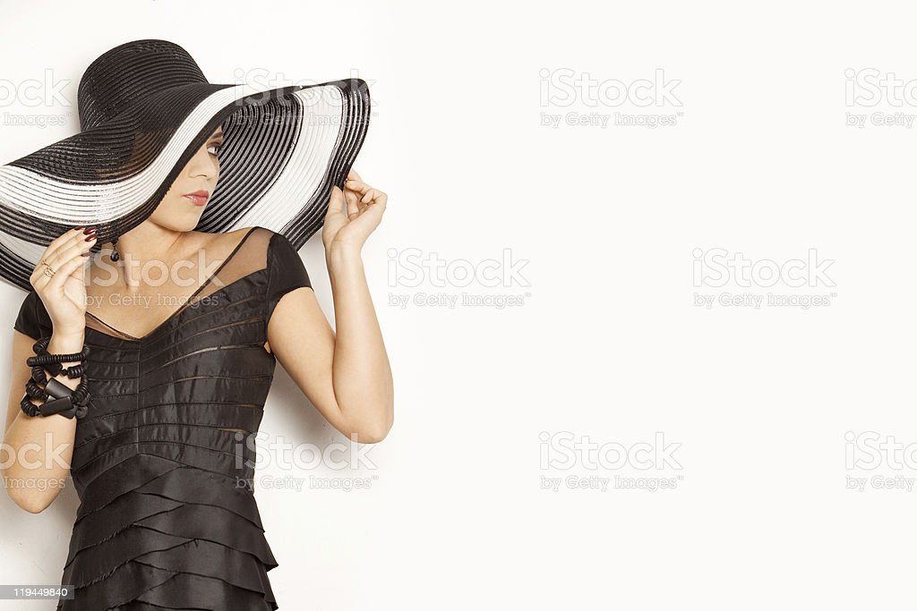 Fashion girl in a big hat on the white background stock photo