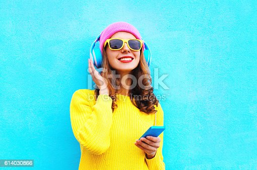 istock Fashion girl listening to music in headphones with smartphone colorful 614030866